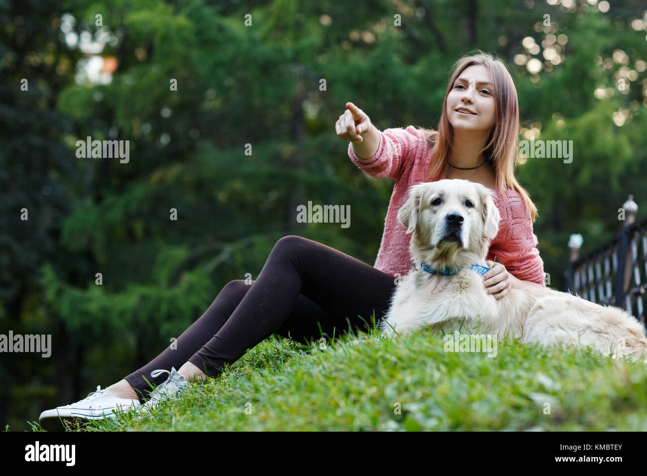 Photo from below of woman pointing forward next to dog on green lawn - Stock Image