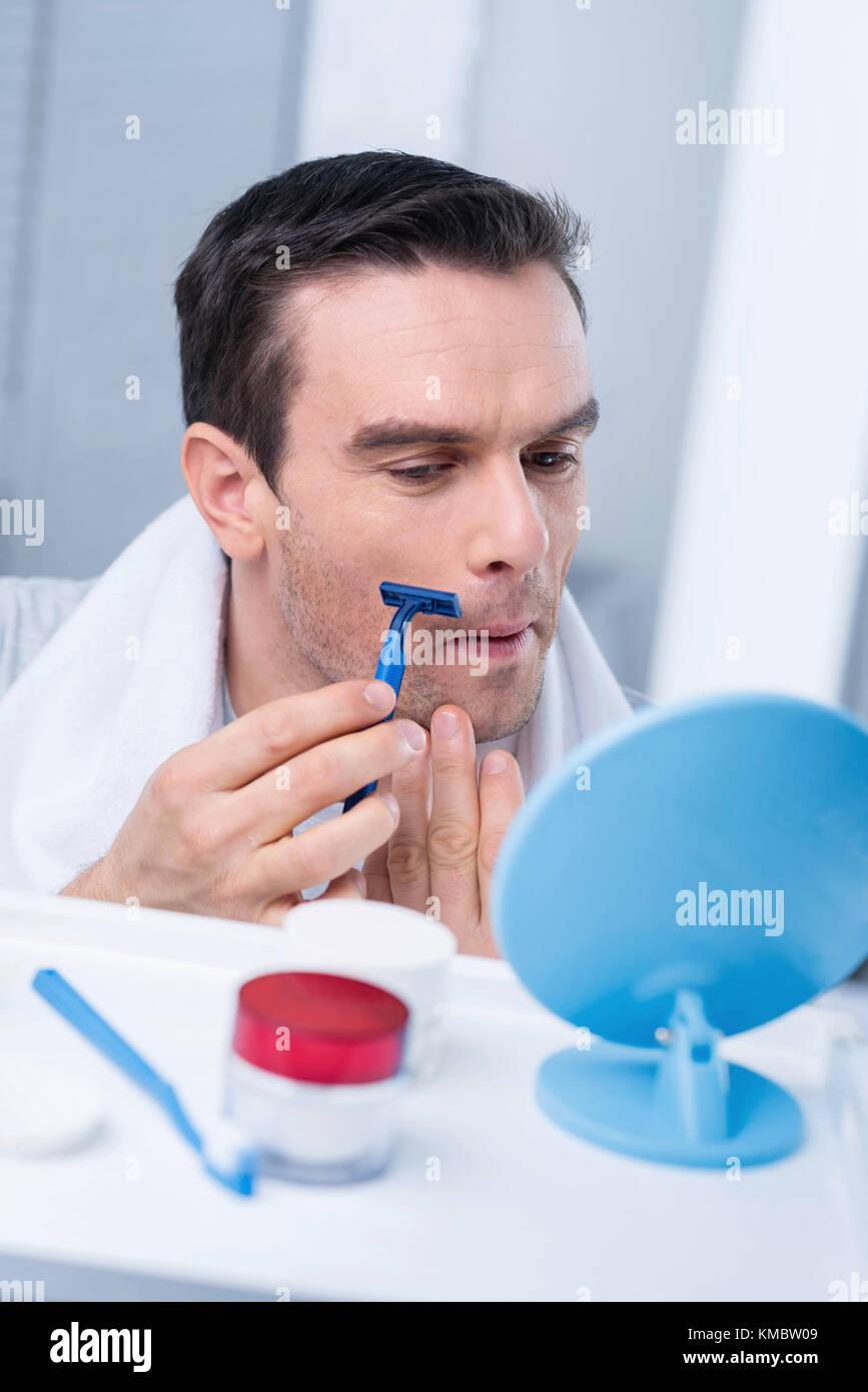 Focused attractive man getting rid of bristles Stock Photo