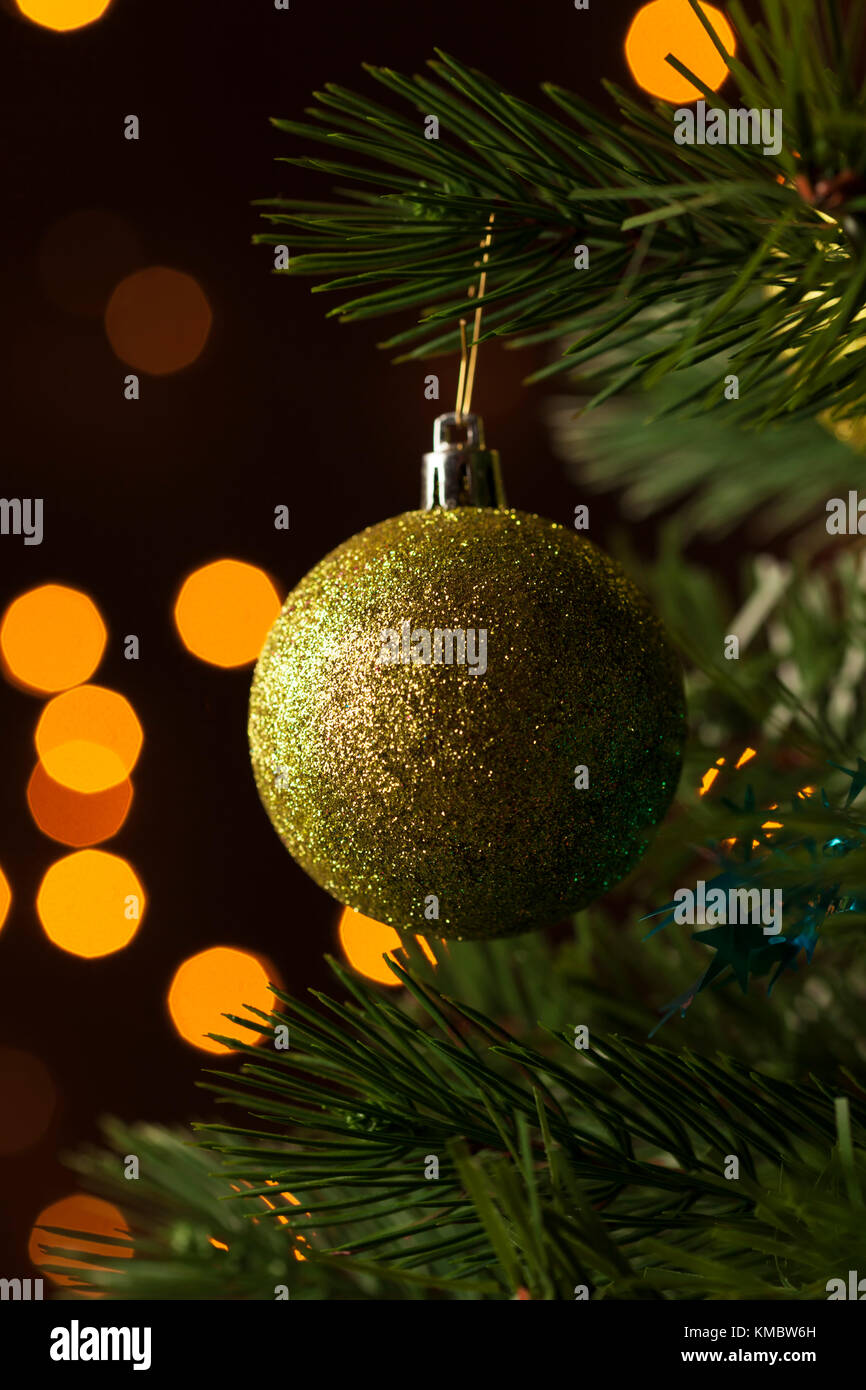 Closeup of glittering golden bauble hanging in christmas tree - Stock Image