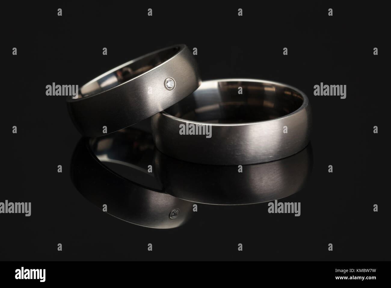 Platinum wedding rings on reflective black surface - Stock Image