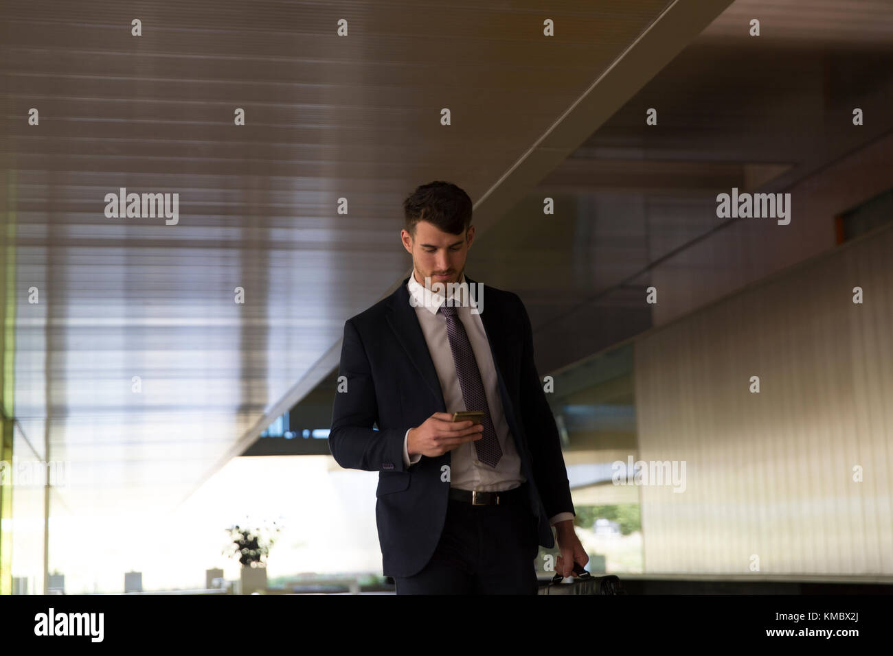 Businessman texting with smart phone in office lobby - Stock Image