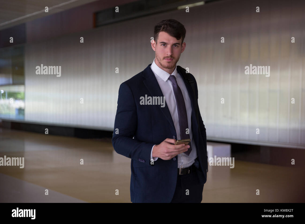 Portrait confident, serious businessman texting with smart phone in office lobby - Stock Image