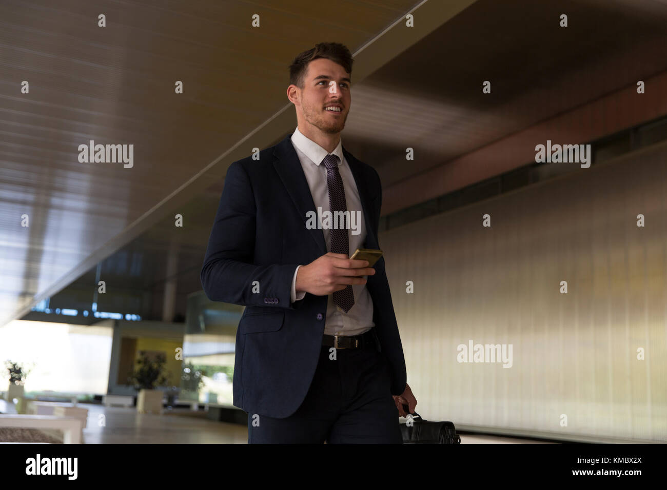 Businessman walking with smart phone in office lobby - Stock Image