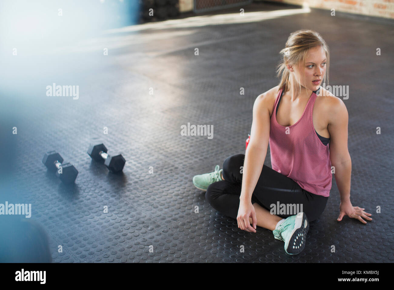 Young woman stretching, twisting in gym next to dumbbells - Stock Image