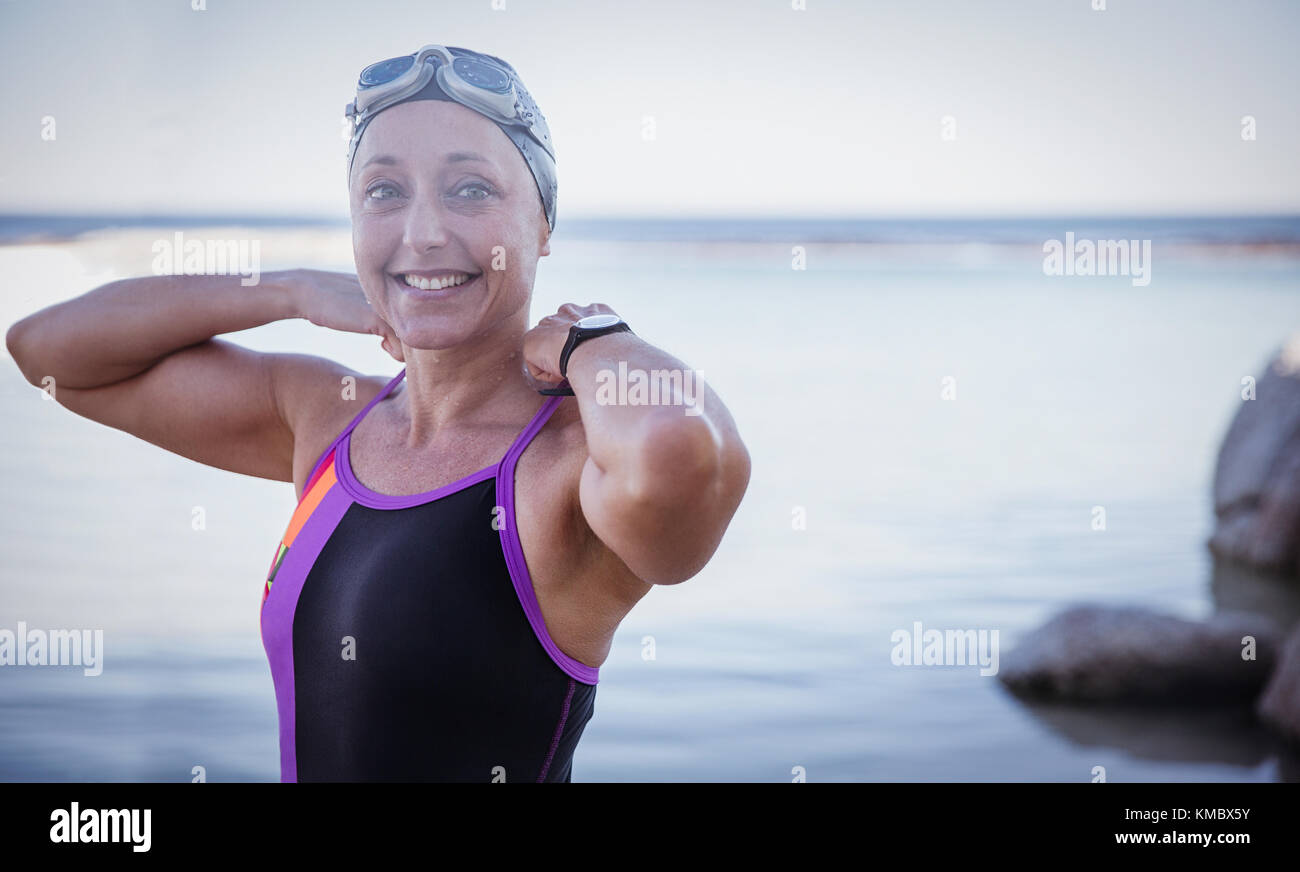 Portrait smiling female open water swimmer adjusting bathing suit in ocean - Stock Image