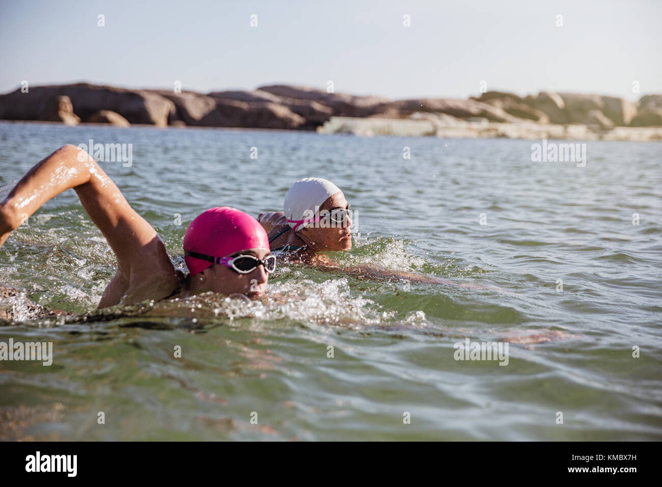 Determined, focused female open water swimmers swimming in sunny ocean - Stock Image