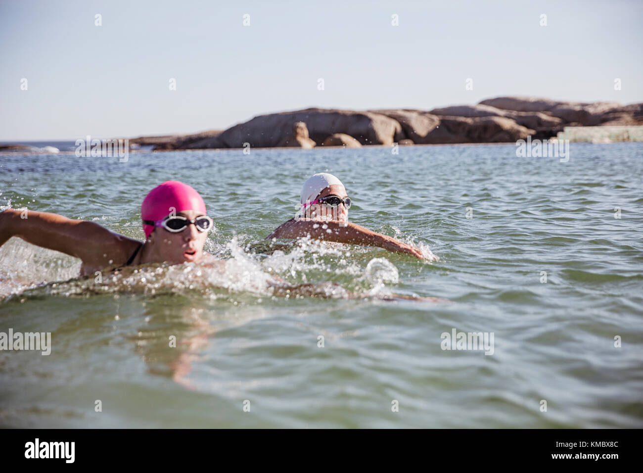 Determined, focused open water swimmers swimming in sunny ocean - Stock Image