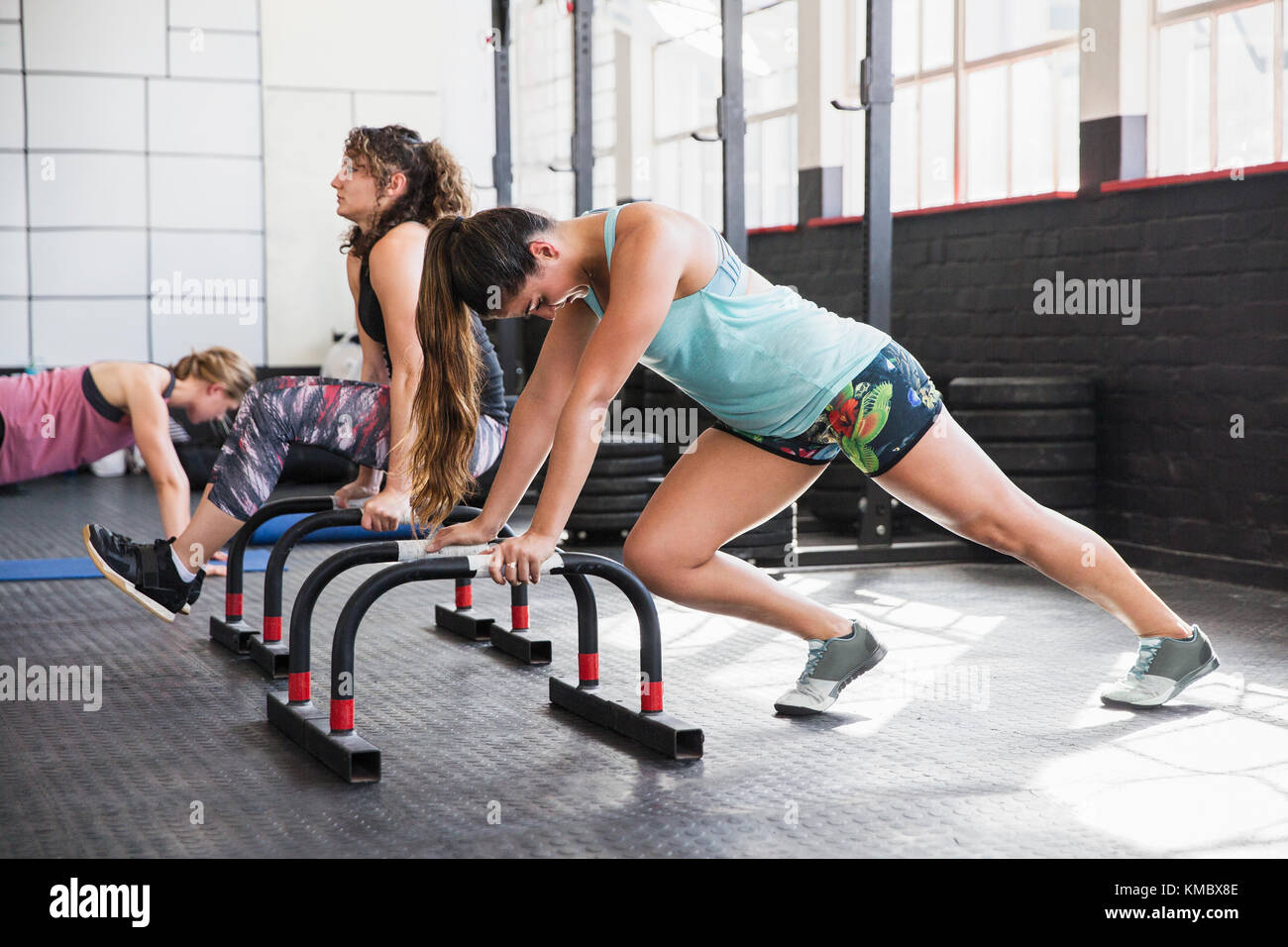 Young woman stretching legs at equipment in gym - Stock Image