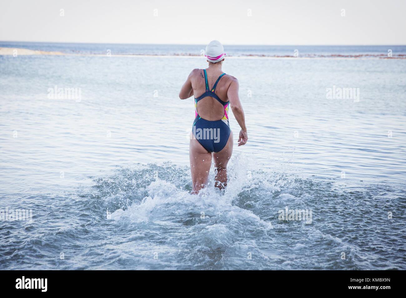 Female open water swimmer running into ocean surf - Stock Image