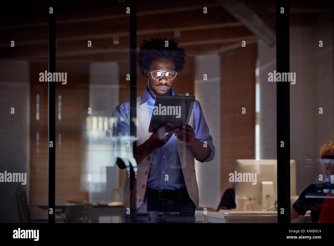 Design professional working late,using digital tablet in dark office at night - Stock Image