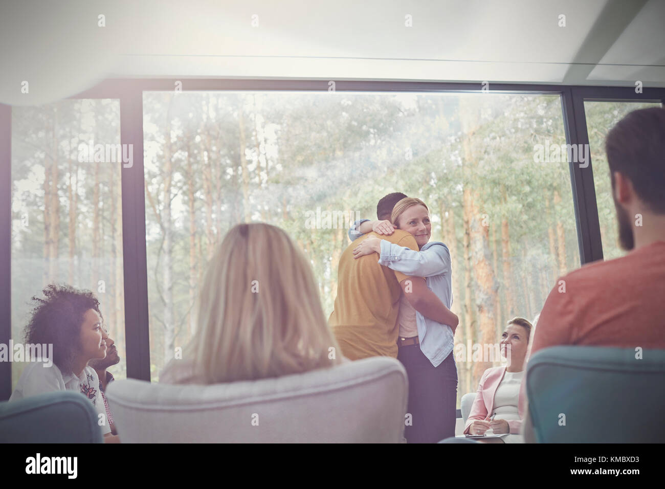 Man and woman hugging in group therapy session - Stock Image