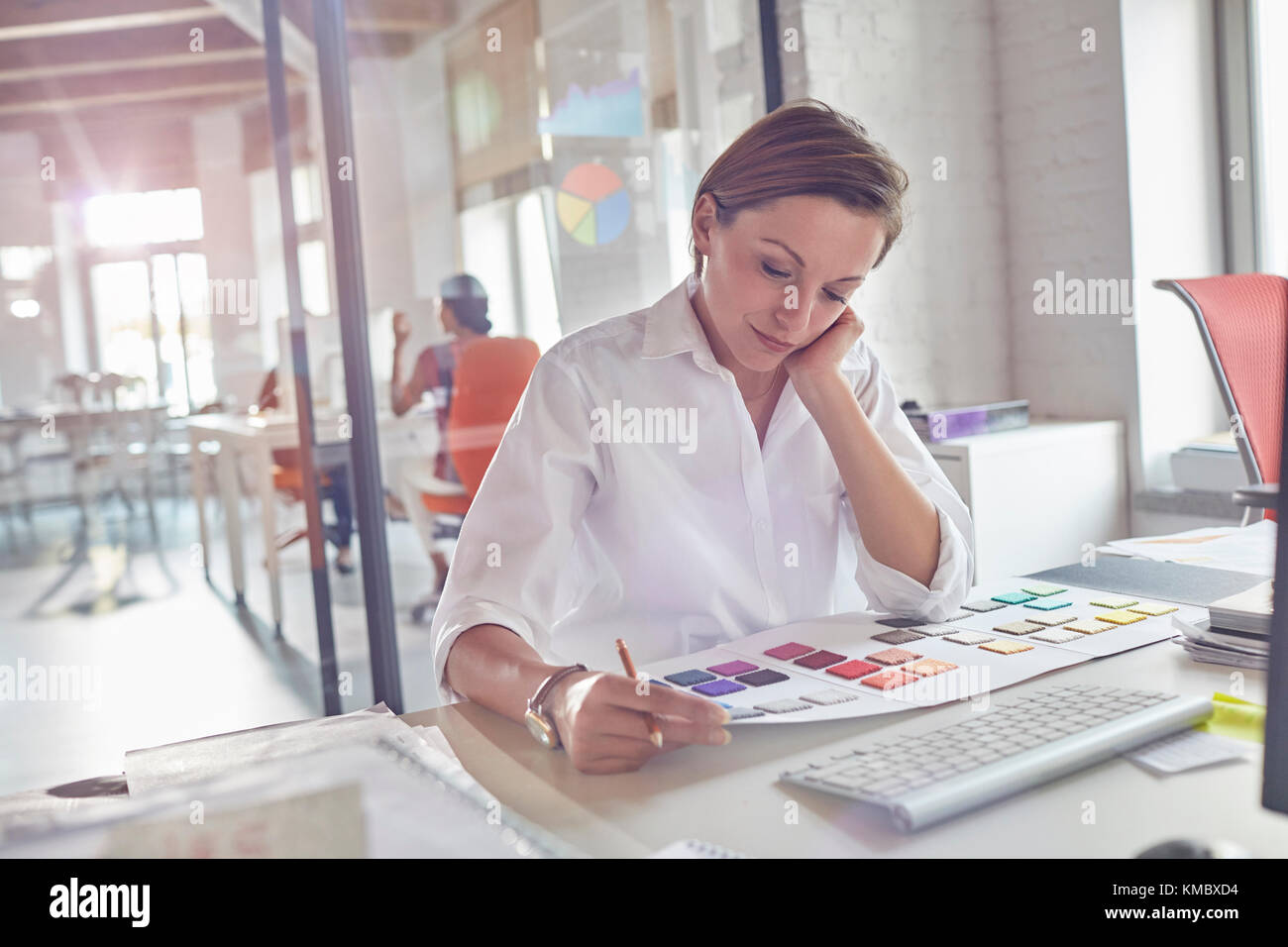 Female design professional reviewing color swatches in office Stock Photo