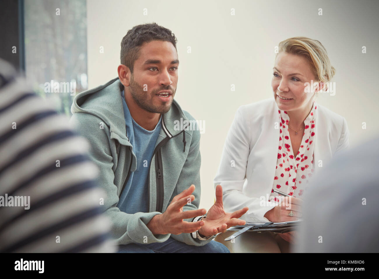 Young man talking in group therapy session - Stock Image