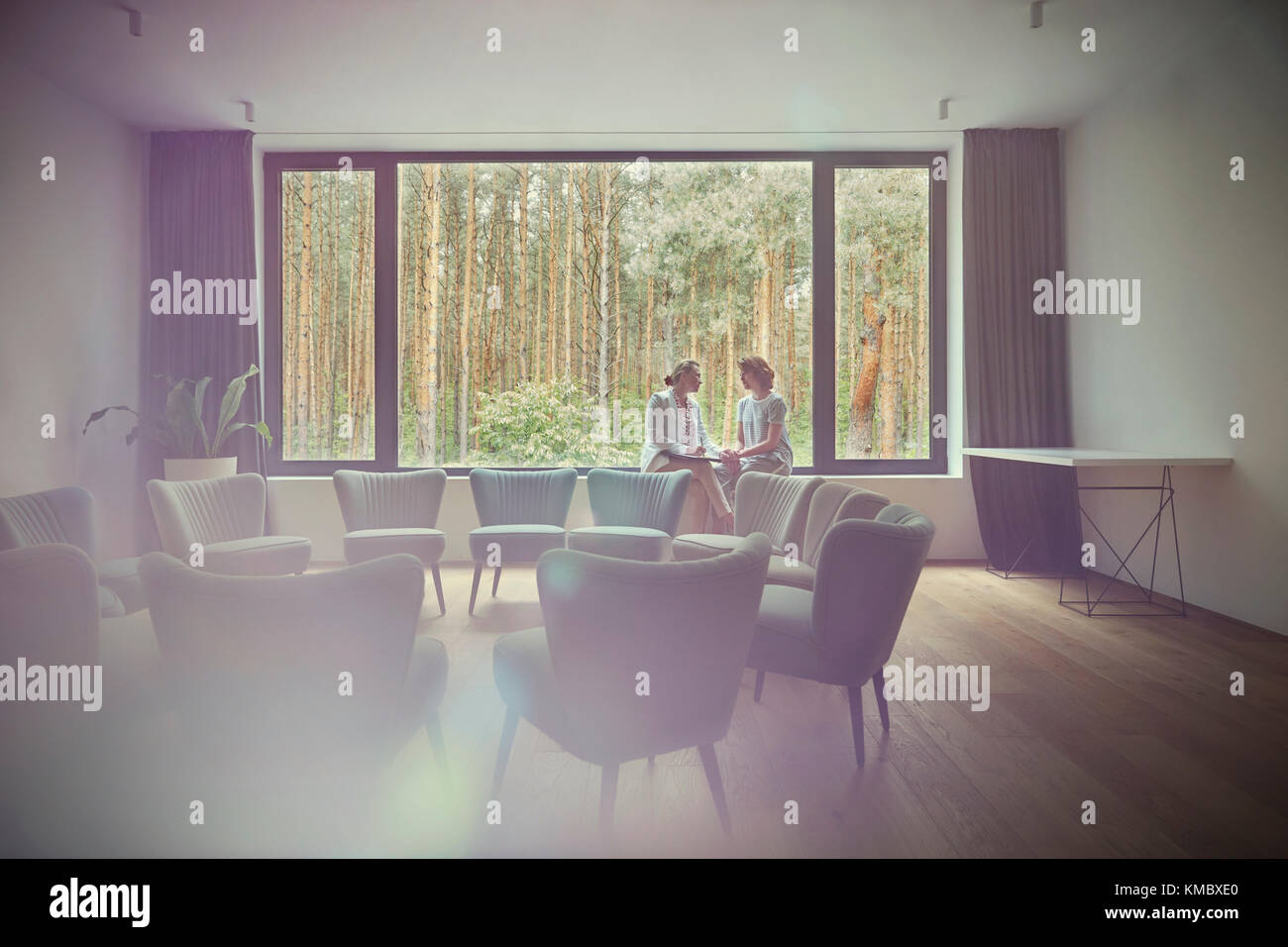 Women talking at window in group therapy room - Stock Image