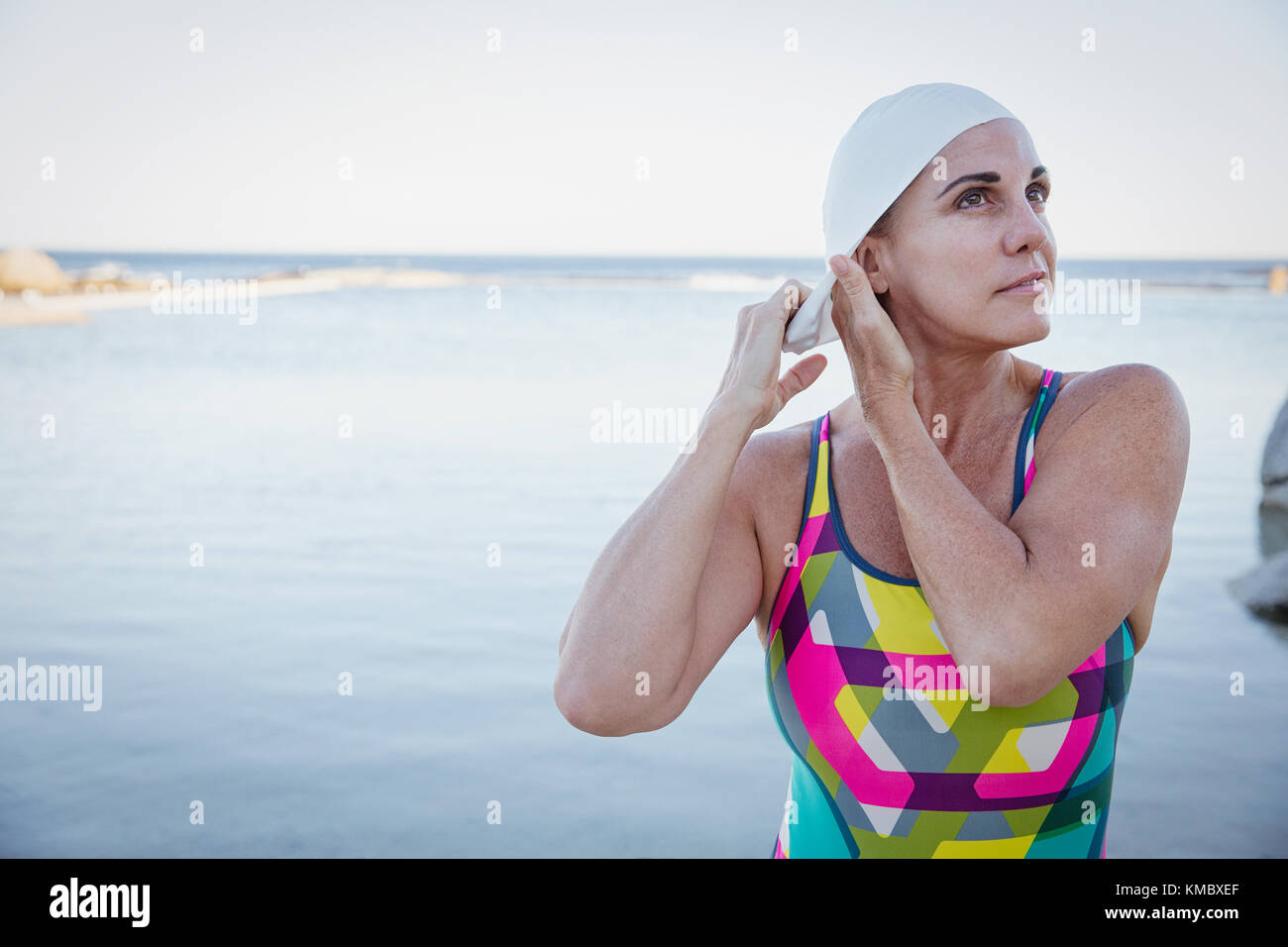 Female open water swimmer adjusting swimming cap at ocean - Stock Image