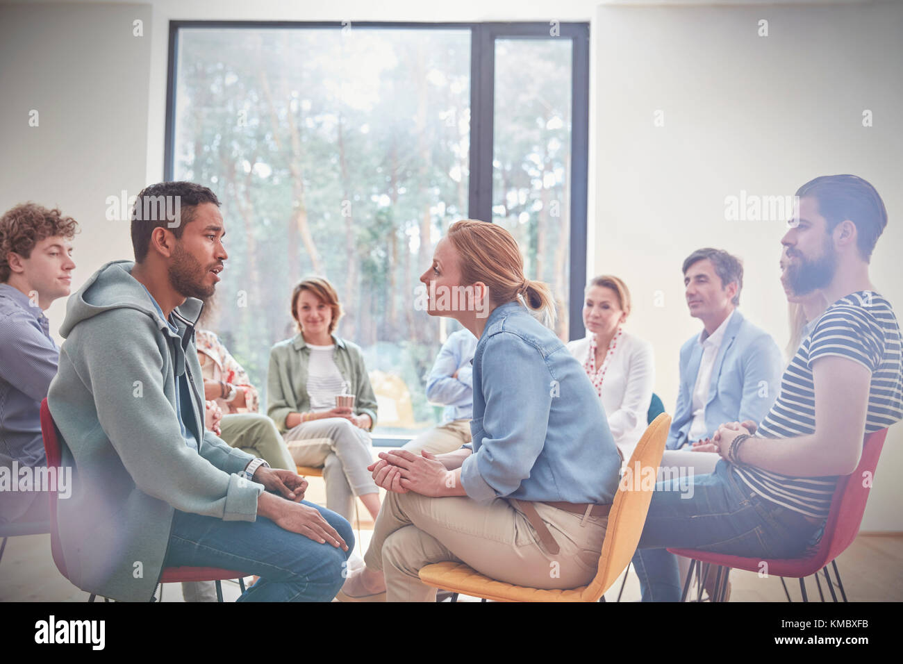 Group watching man and woman talking face to face in group therapy session - Stock Image