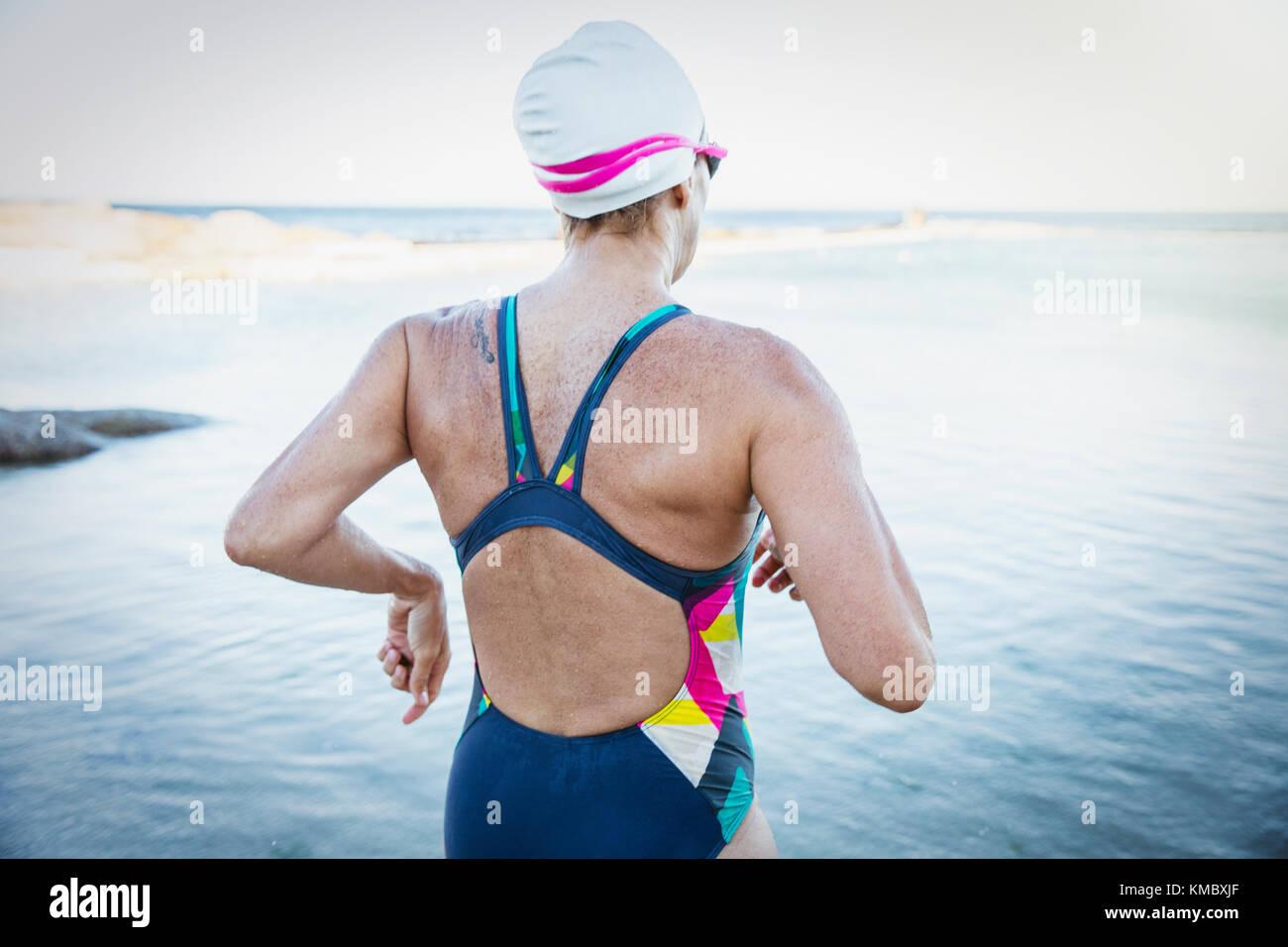 Female open water swimmer running into ocean - Stock Image