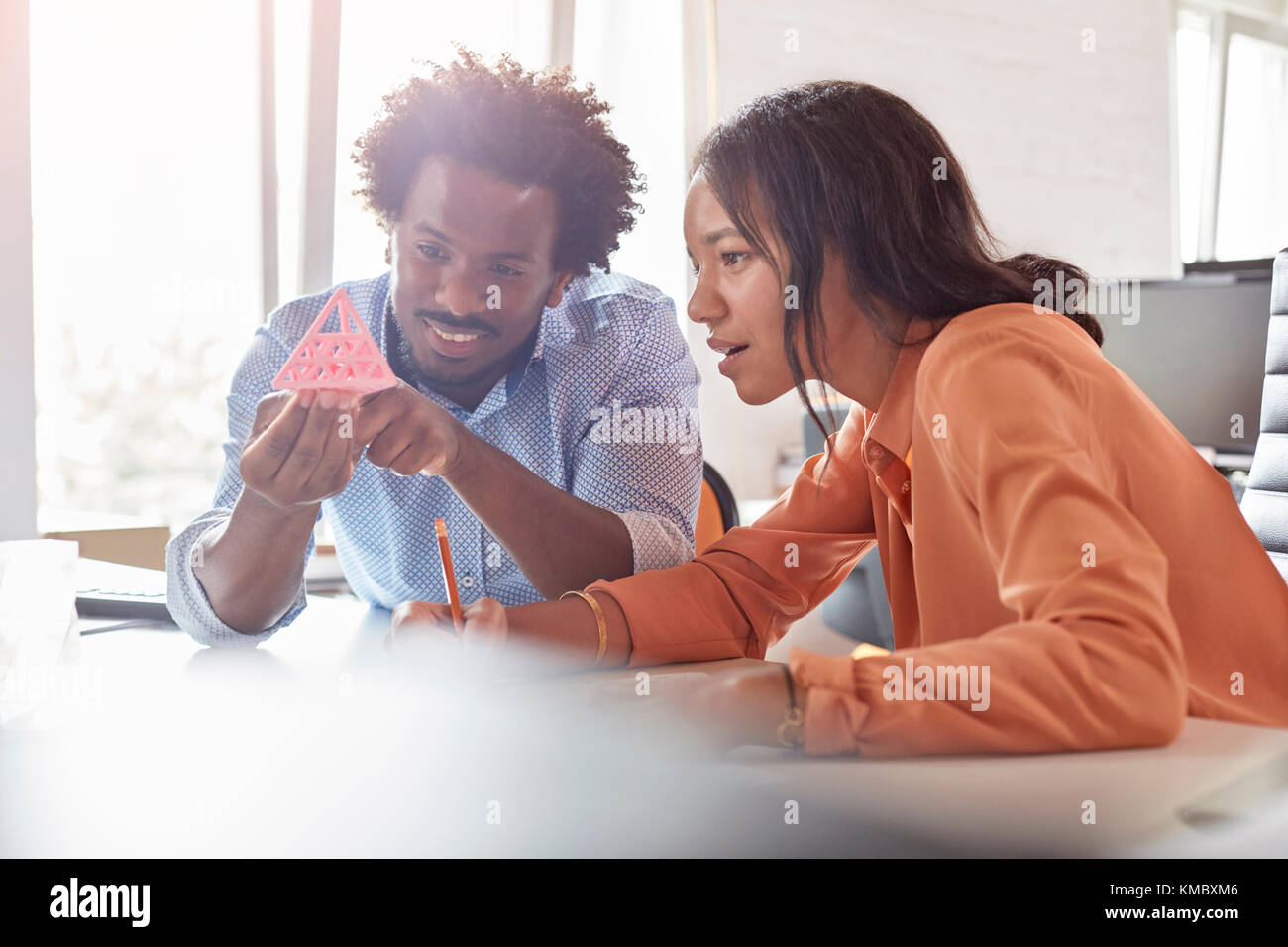 Design professionals examining triangle prototype in office Stock Photo