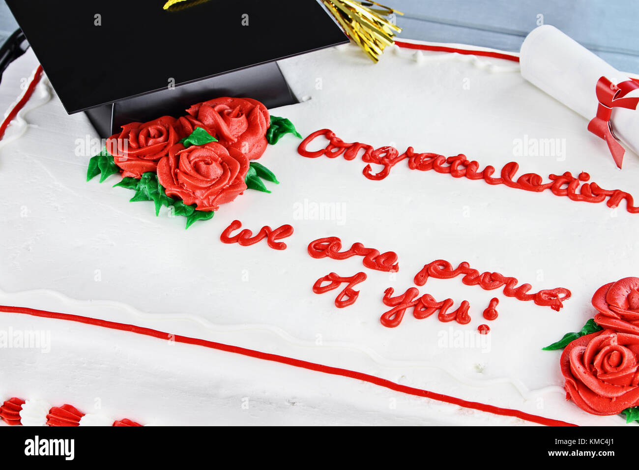 Vanilla graduation cake with school cap, tassel, diploma and red roses with text. Room for copy space. - Stock Image