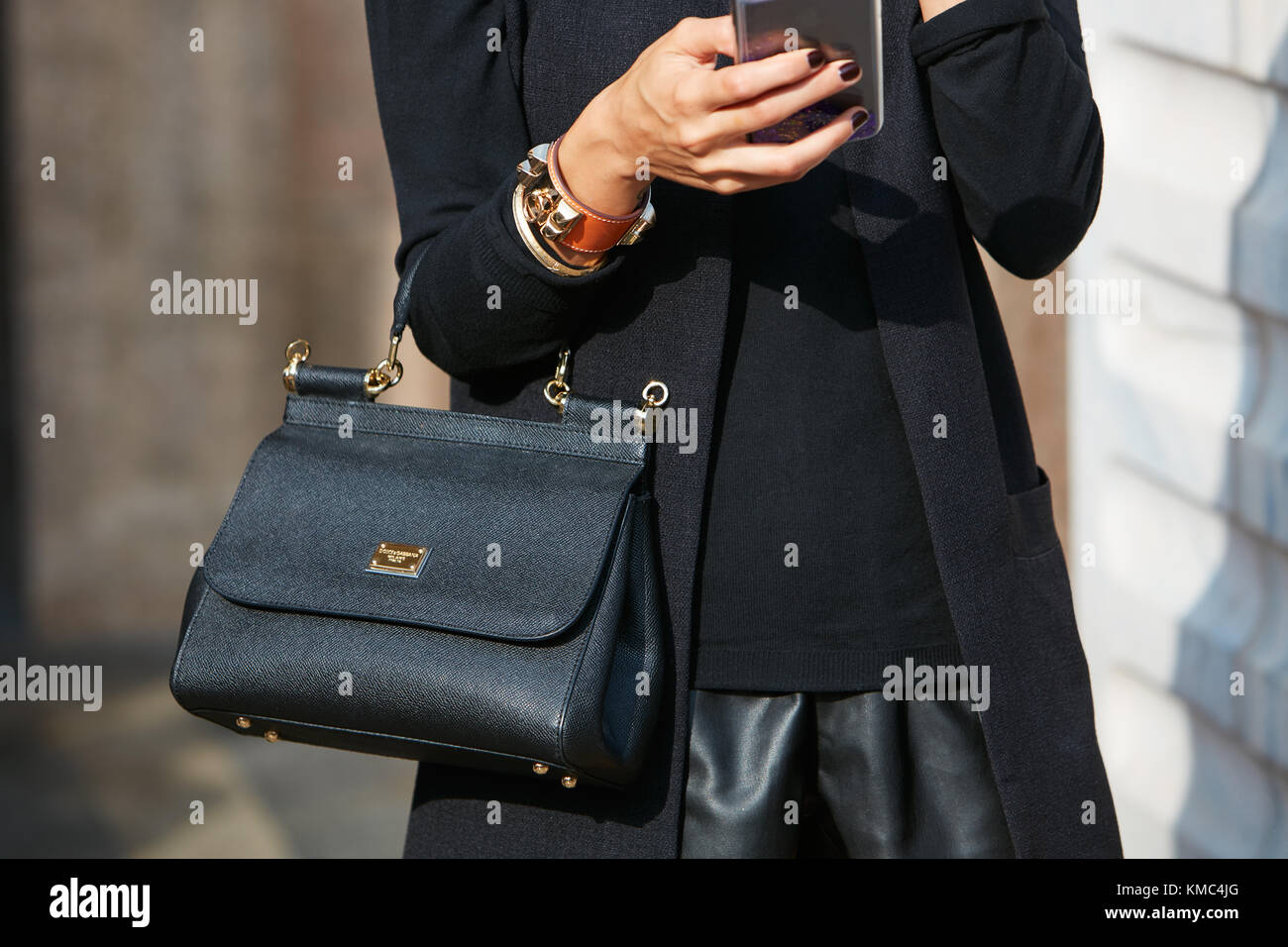 MILAN - SEPTEMBER 23: Woman with Dolce and Gabbana black leather bag and bracelet with golden studs before Gabriele - Stock Image