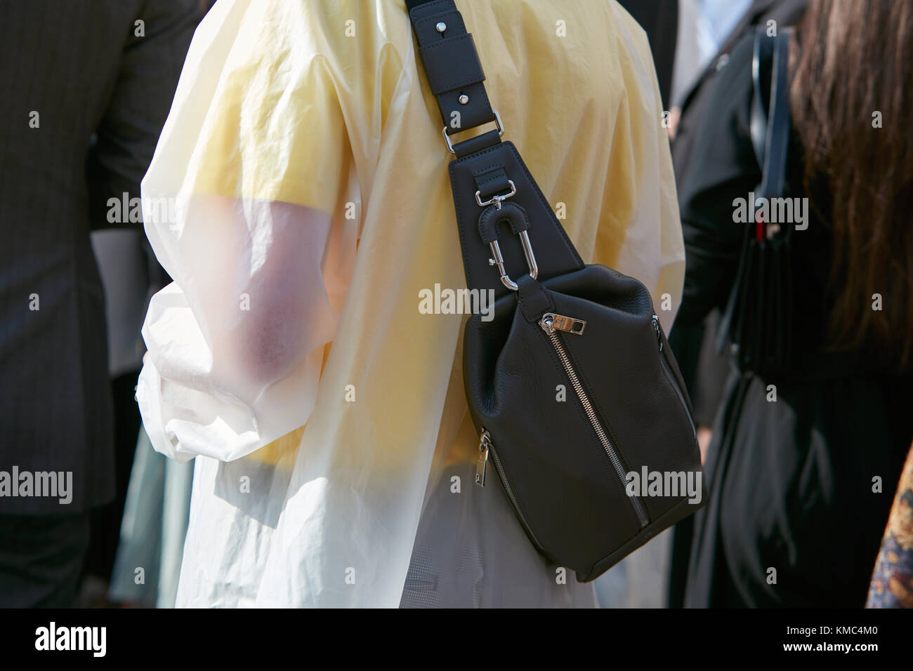 MILAN - SEPTEMBER 23: Woman with black leather pouch and transparent raincoat before Gabriele Colangelo fashion - Stock Image