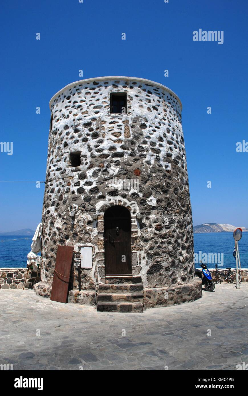 An old stone tower on the seafront at Mandraki on the Greek island of Nisyros on June 12, 2010. - Stock Image
