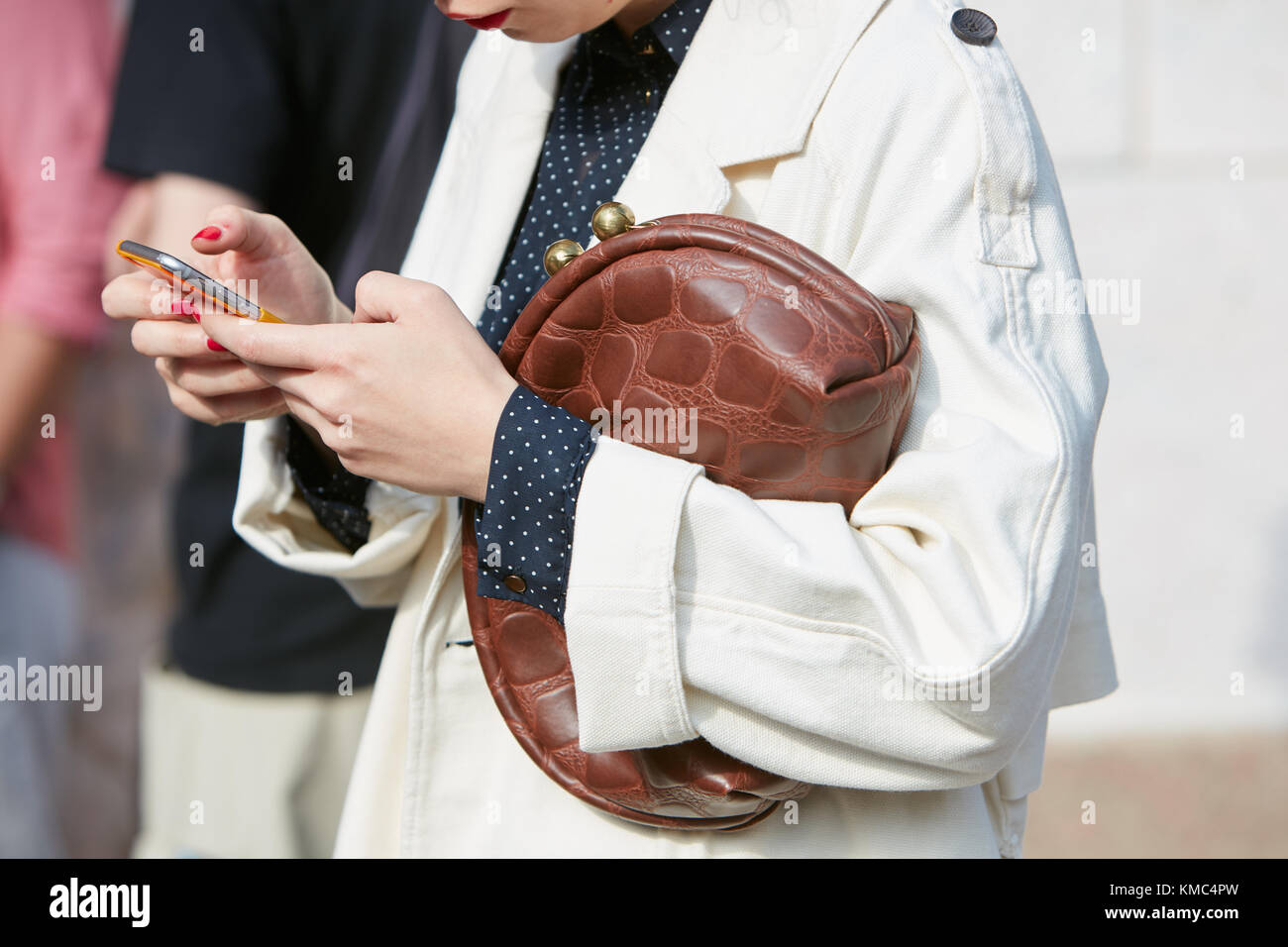 MILAN - SEPTEMBER 23: Woman with brown reptile bag and white trench coat looking at smartphone before Gabriele Colangelo - Stock Image