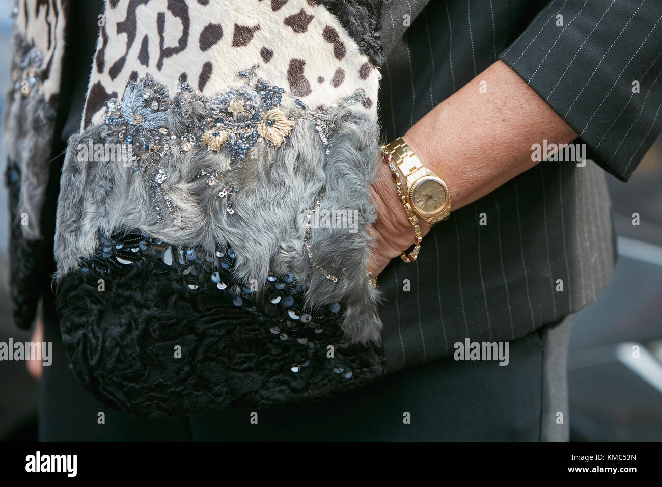 b88bf8ddc35104 MILAN - SEPTEMBER 23: Woman with yellow gold Rolex Datejust and pinstripe  and fur jacket before Antonio Marras fashion show, Milan Fashion Week street