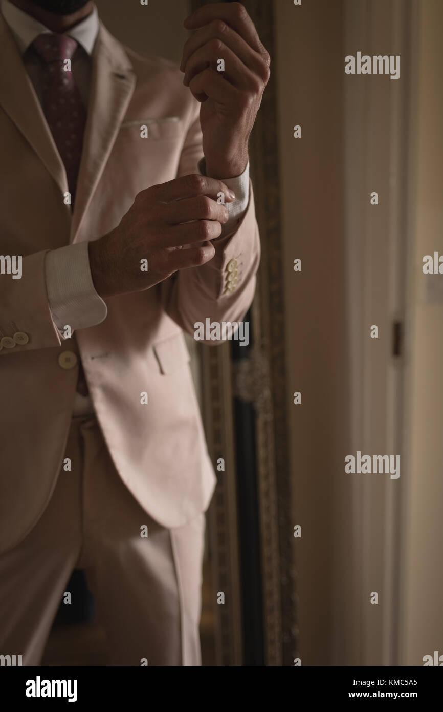 Man wears cuff-links on a shirt sleeve - Stock Image