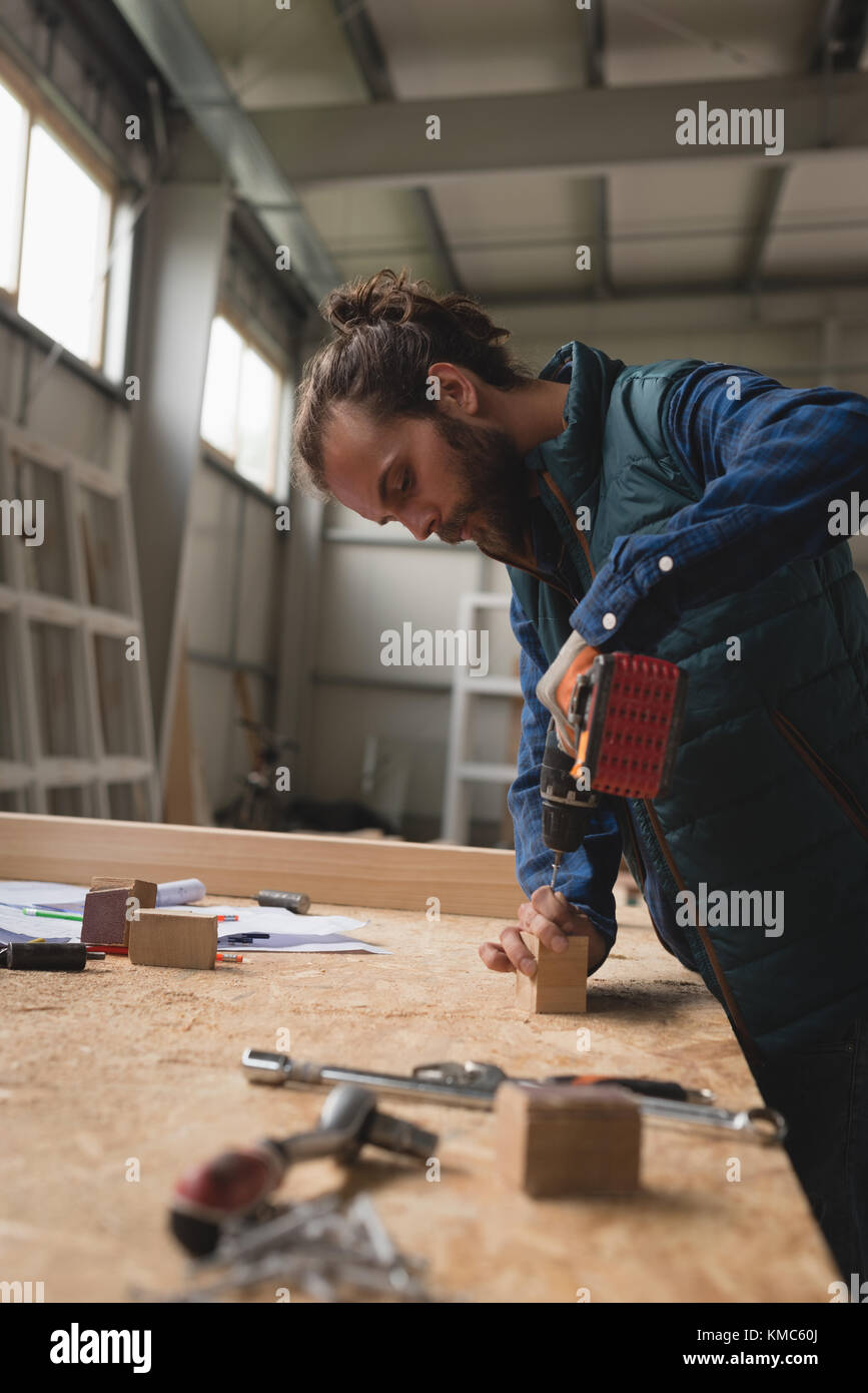 Carpenter making hole in wooden block with screw gun - Stock Image