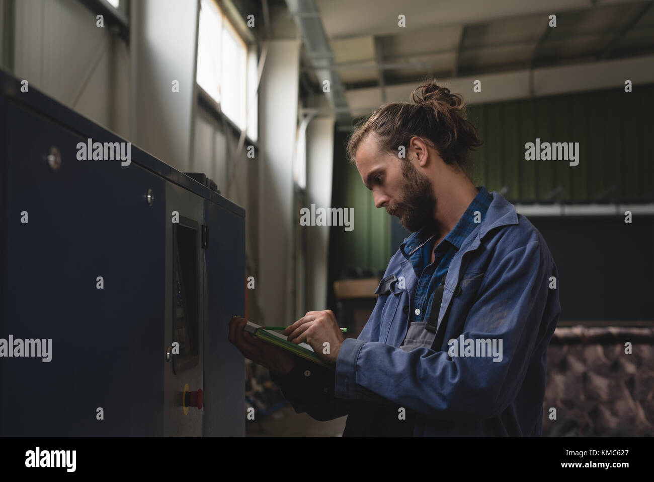 Mechanic maintaining record on clipboard - Stock Image