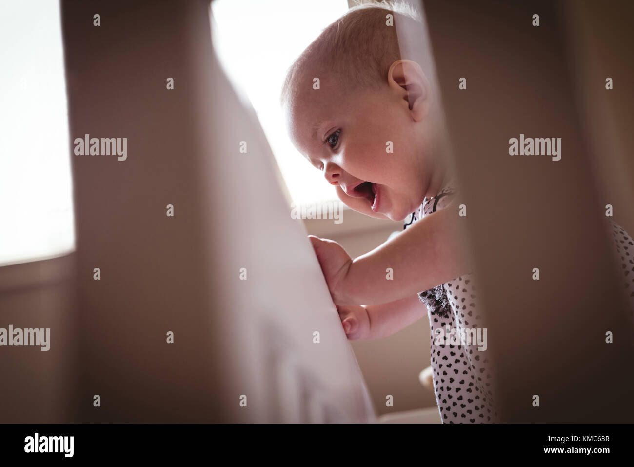 Cute girl standing in cot - Stock Image
