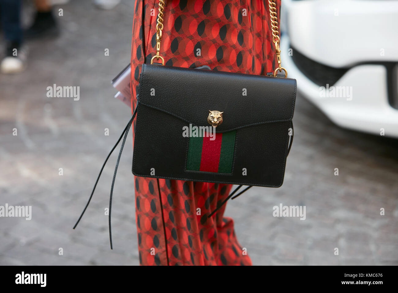 ee2ed2eaeda9 MILAN - SEPTEMBER 23: Woman with black leather Gucci bag with red and green  stripes and golden lion head before Antonio Marras fashion show, Milan Fas
