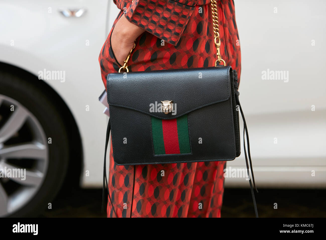 65d503f07bb4 MILAN - SEPTEMBER 23: Woman with black leather Gucci bag with golden lion  head and red dress before Antonio Marras fashion show, Milan Fashion Week st