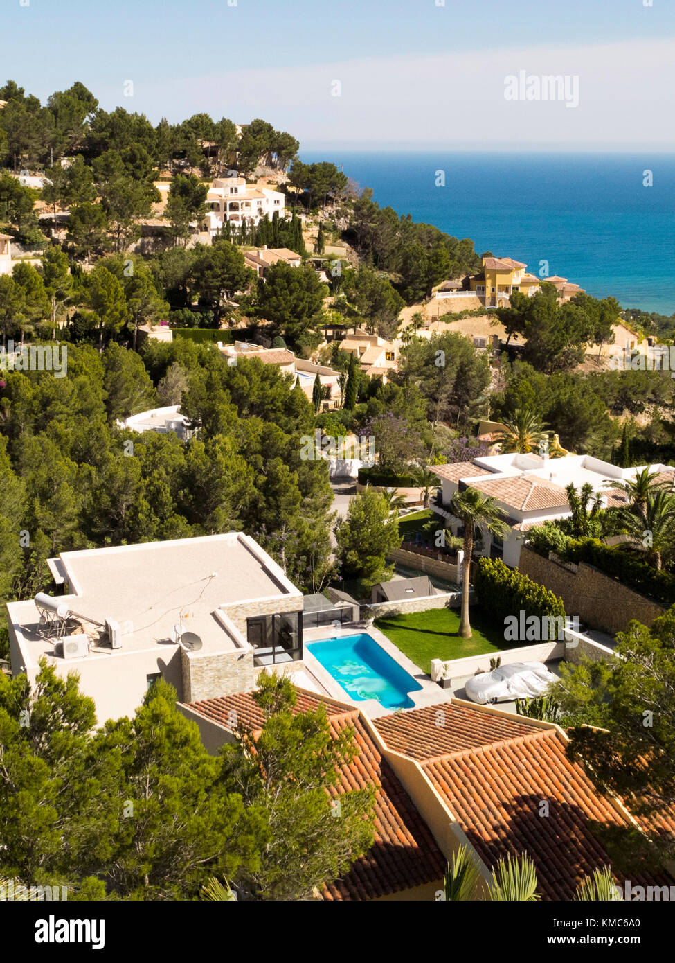 car  protected under tarp next to swimming pool in luxury villa surrounded by Mediterranean style villas in urbanization Stock Photo