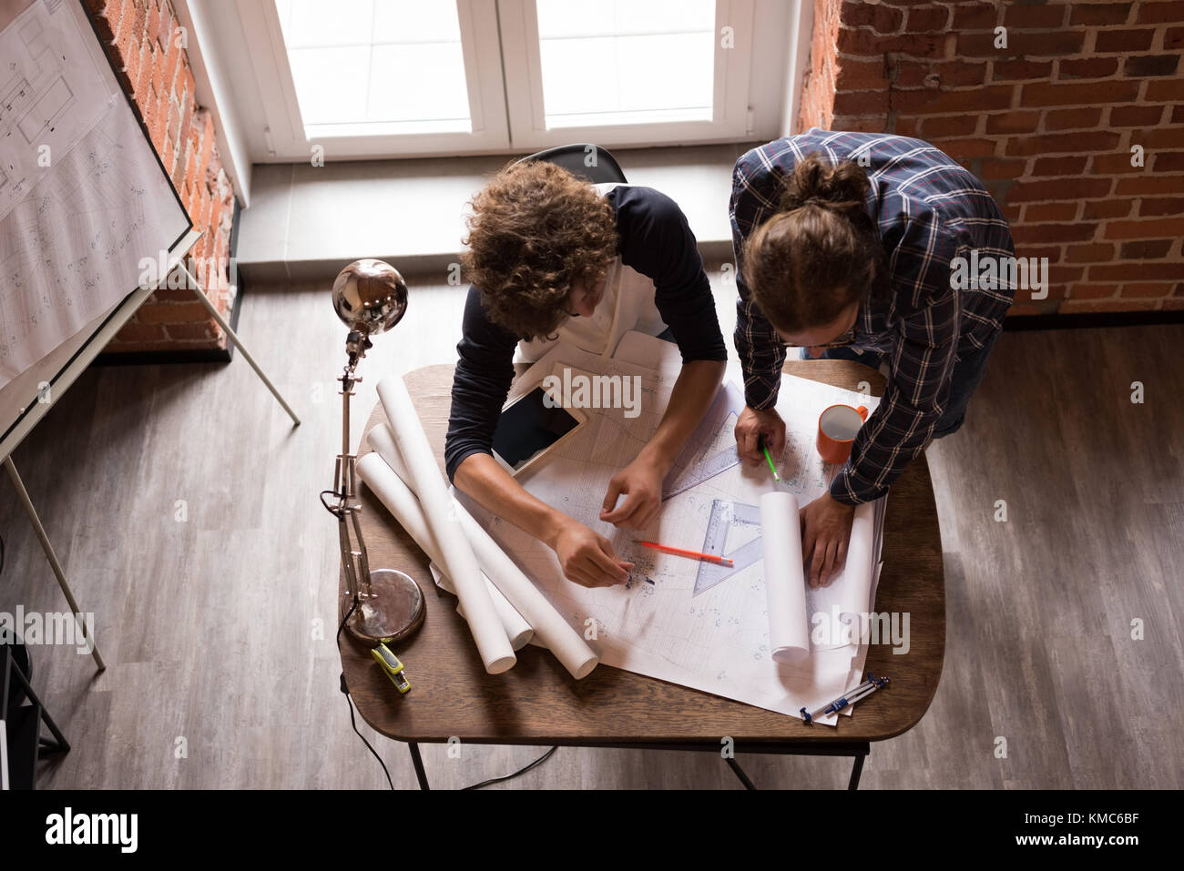 Male graphic designers working on blueprint - Stock Image