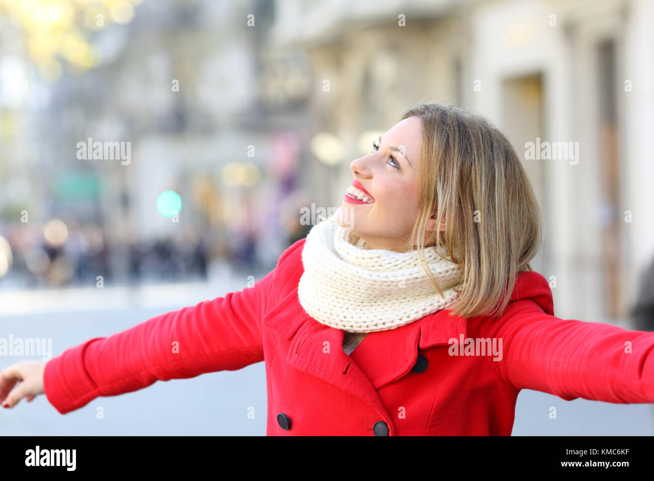 Portrait of a candid woman wearing a red coat joking on the street and looking at side   in winter - Stock Image