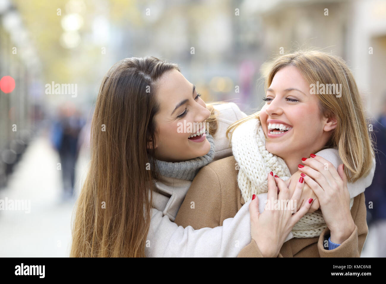 Two happy friends joking and laughing on the street in winter - Stock Image