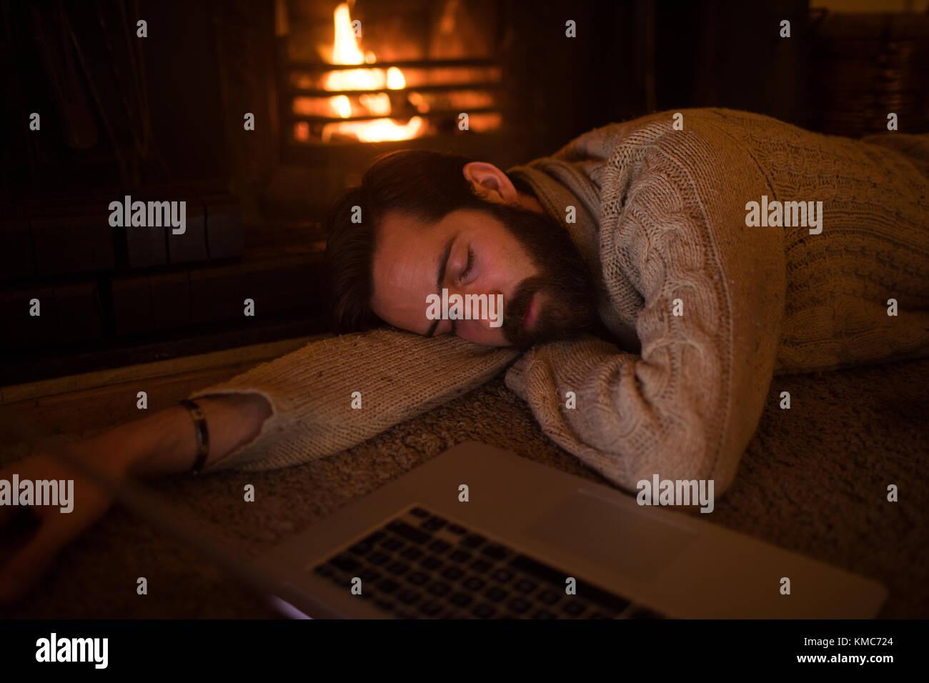 Man sleeping on floor in living room - Stock Image
