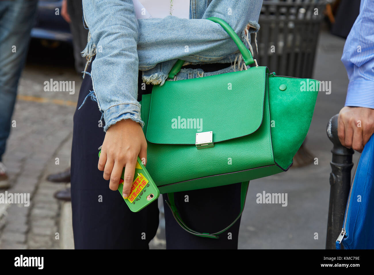 MILAN - SEPTEMBER 23  Woman with Celine green leather bag and blue jeans  torn jacket before Blumarine fashion show 5893c81928551