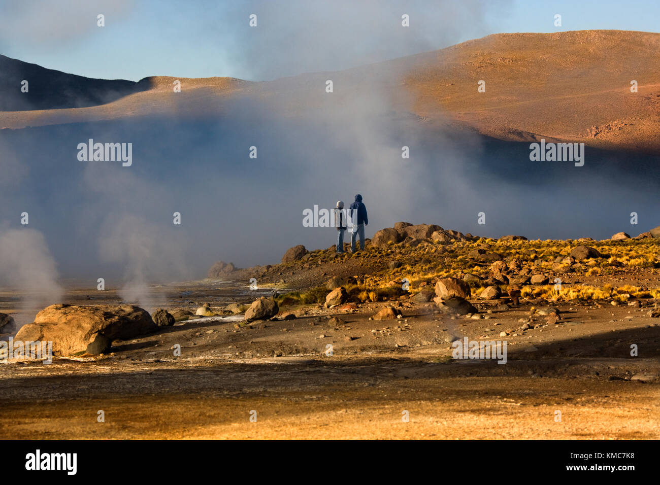 Adventure tourists at the Geo-thermal steam vents at El Tatio Geyser Field. El Tatio is located within the Andes - Stock Image