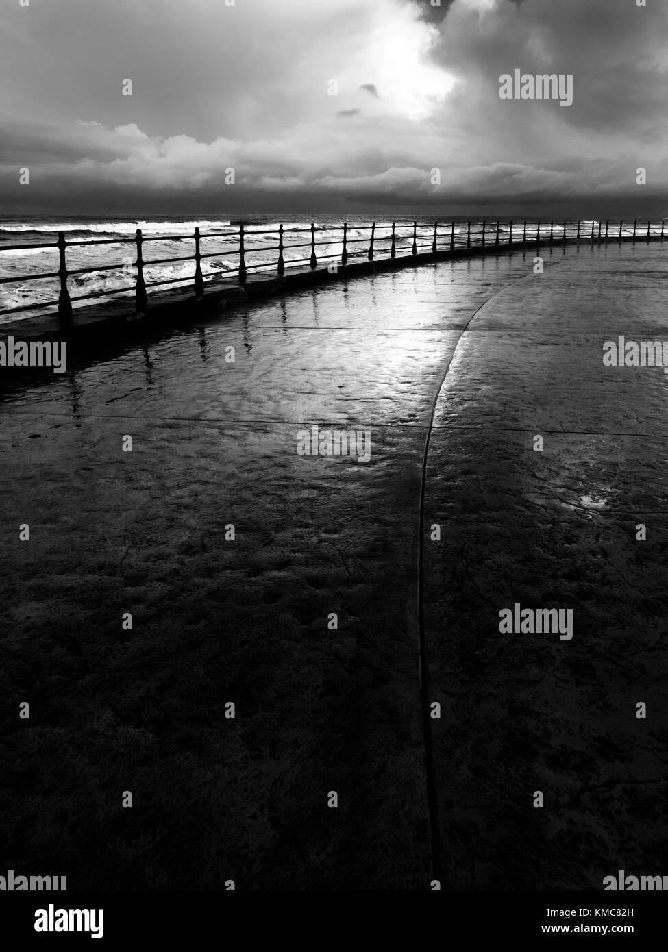 Iron Railings on the Sea Wall and Reflections after Rain in Souith Bay Scarborough North Yorkshire England - Stock Image