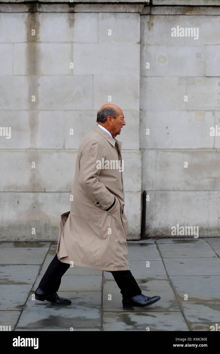 Caucasian man wearing trench coat with hands in pockets walking through Trafalgar Square, London, England, UK - Stock Image
