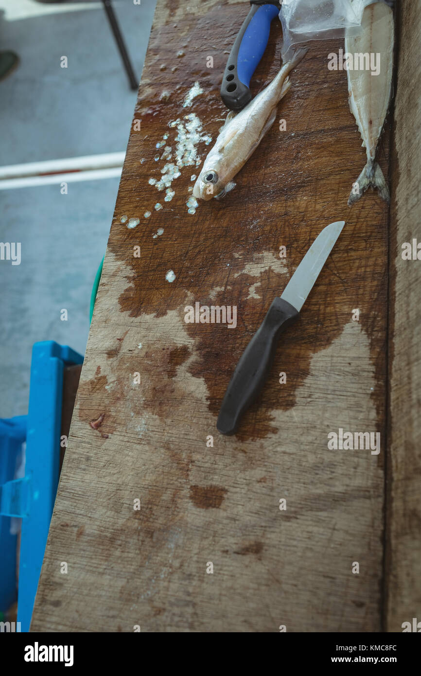Skinned fish and knife on wooden worktop - Stock Image