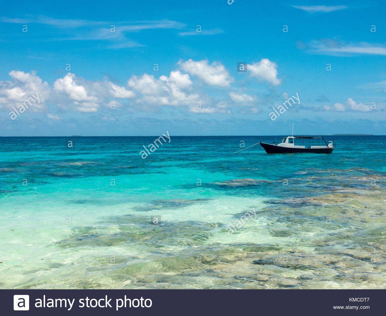 Little boat anchored on shallow water, Kingdom of Tonga - Stock Image