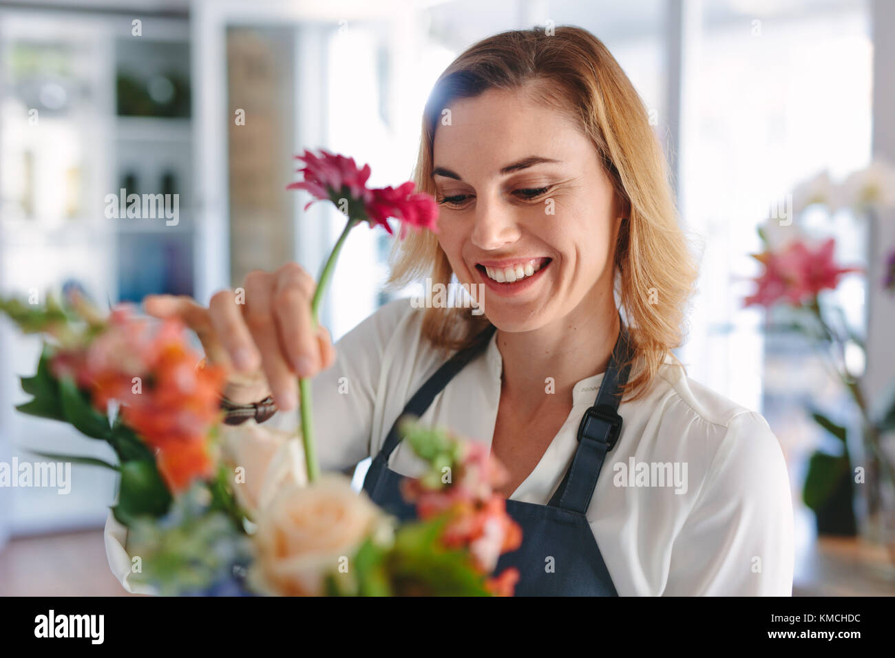 Female florist arranging flowers. Woman flower shop owner placing flowers in a bouquet. - Stock Image