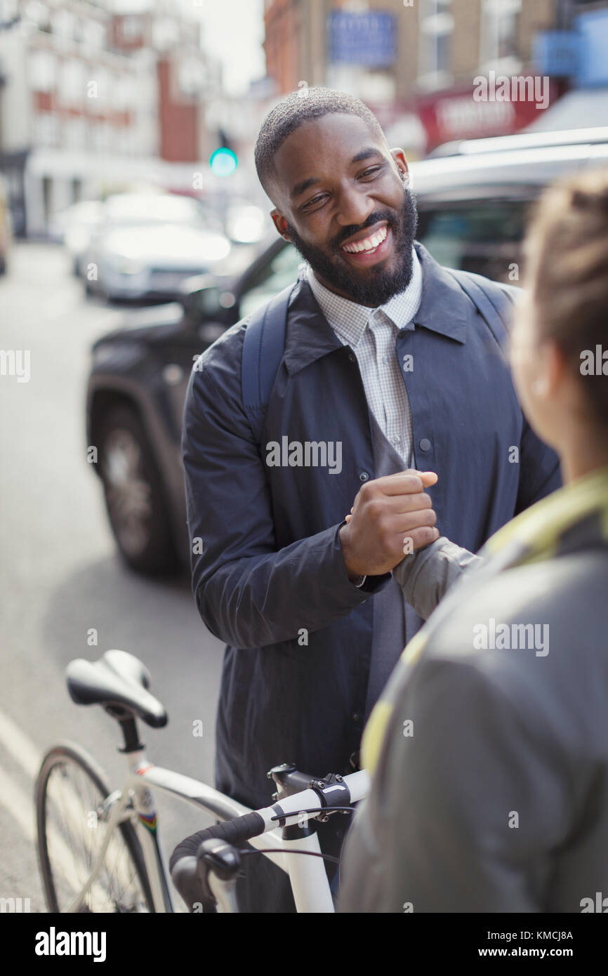 Smiling businessman with bicycle shaking hands with woman on urban street - Stock Image