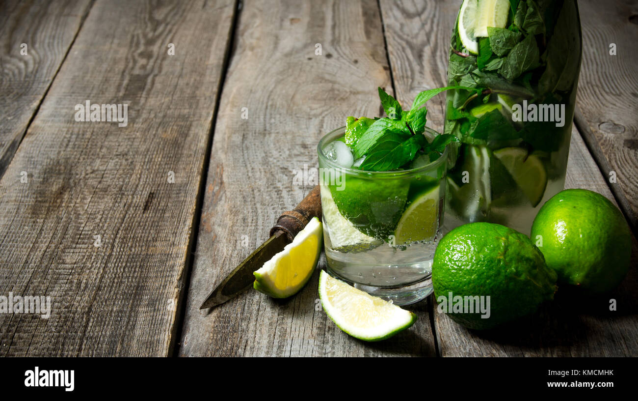 Mojito cocktail . Cocktail in glass and bottle , also mint and limes on a wooden table . Free space for text. - Stock Image
