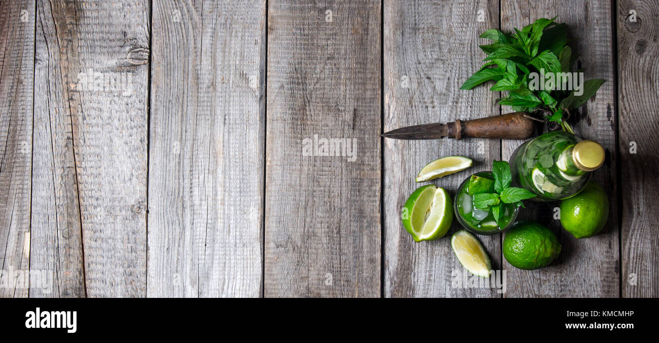 Mojito cocktail . Cocktail in glass and bottle , also mint and limes on a wooden table . Free space for text. Top - Stock Image