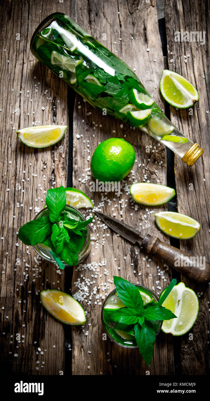 Mojito cocktail . The ingredients for the cocktail - limes, mint, knife, is also prepared cocktail in the bottle - Stock Image